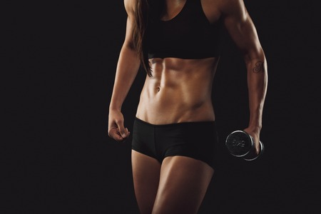 Cropped image of strong and muscular build woman exercising with weights. Female fitness woman on black background