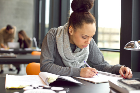 Photo pour Female student taking notes from books for her study. Young african american woman sitting at table with books for finding information. - image libre de droit