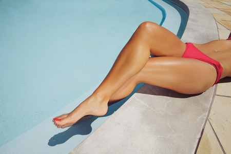 Overhead view of a beautiful female fashion model relaxing on the edge of a pool. Legs crossed of young woman resting by swimming pool.
