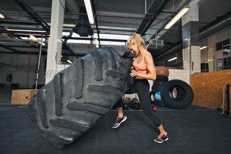 Muscular young woman flipping tire at gym. Fit female athlete performing a tire flip at crossfit gym.