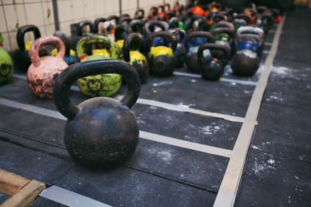 Different sizes of kettlebells weights lying on gym floor. Equipment commonly used for crossfit training at fitness club