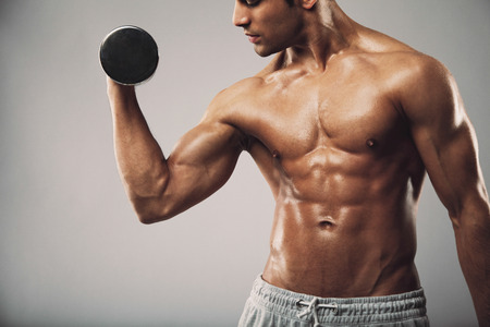Cropped image of young muscular man doing heavy dumbbell exercise for biceps. Man working out with dumbbells on grey . Fitness and workout concept.