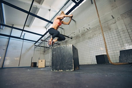 Low angle view of young female athlete box jumping at a crossfit gym. Fit woman is performing box jumps at gym.
