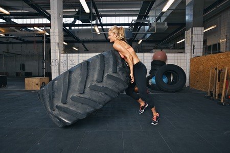 Fit female athlete flipping a huge tire. Muscular young woman doing crossfit exercise at gym.