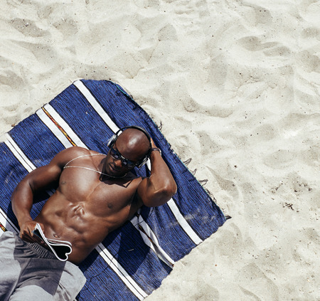 Image of muscular young man lying on a mat reading magazine. Shirtless male model relaxing on beach.