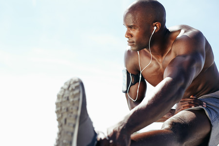 Foto de Image of muscular young man working out against sky. African man looking away with stretching his leg. Shirtless male model exercising outdoors. - Imagen libre de derechos