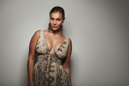 Portrait of a attractive young woman looking sensually at camera. Voluptuous female model posing a beautiful dress against grey background with copy space.