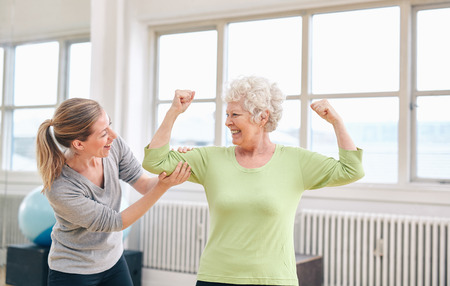 Portrait of female trainer looking at elderly woman flexing her bicep at the rehabilitation center. Happy about her recovery at rehab.