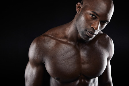 Close-up image of young man with muscular build. Shirtless african male model with looking at camera on black background.