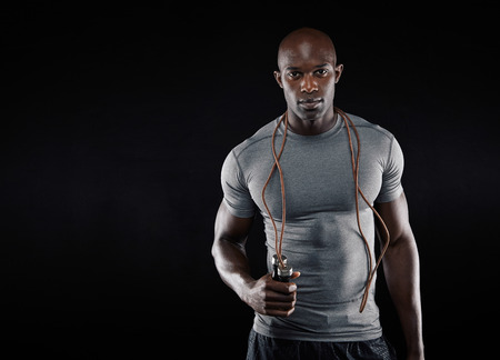 Foto de Handsome muscular man with jumping rope on black background. Fit african model with lots of copy space. - Imagen libre de derechos