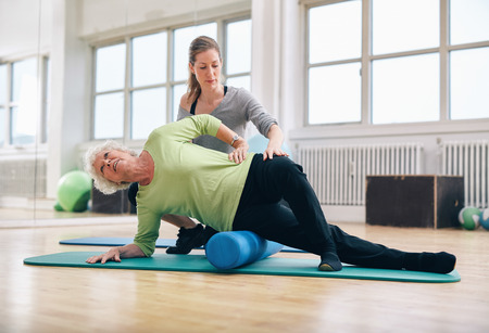 Female instructor helping senior woman using a foam roller for a myofascial release massage at gym.