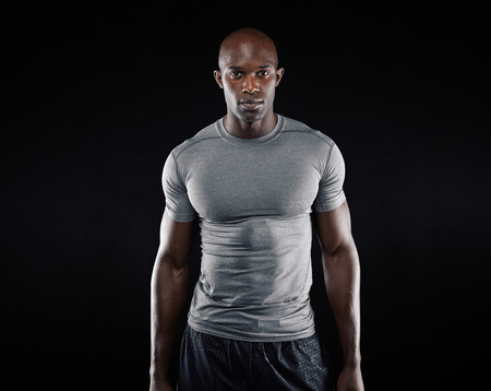 Portrait of fit young man with muscular build standing against black background. Afro american fitness model.