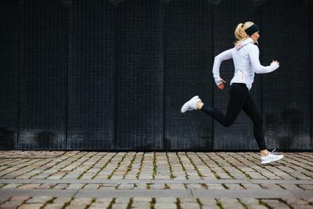 Foto de View of young woman running on sidewalk in morning. Health conscious concept with copy space. - Imagen libre de derechos