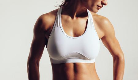 Foto de Portrait of fit woman in sports bra with muscular body against grey background. Close-up studio shot of female fitness model in sports wear. - Imagen libre de derechos