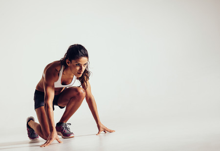 Foto de Female athlete in position ready to run over grey background. Determined young woman ready for a sprint. - Imagen libre de derechos