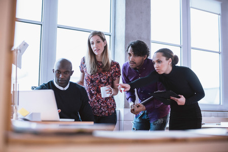Photo pour Portrait of a modern business team working at new project during meeting and looking at laptop. Multiracial business people working together. - image libre de droit