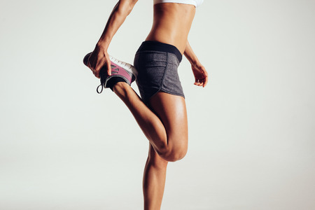 Photo for Cropped image of a fitness woman stretching her legs against grey background.  Fit female runner doing stretches. - Royalty Free Image