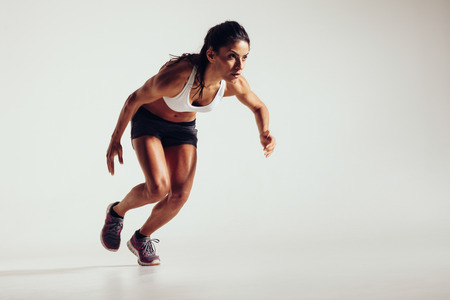 Foto de Young woman starting to run and accelerating over grey background. Powerful young female athlete running in competition. - Imagen libre de derechos