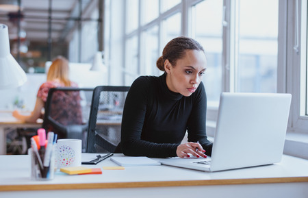Photo for Image of woman using laptop while sitting at her desk. Young african american businesswoman sitting in the office and working on laptop. - Royalty Free Image