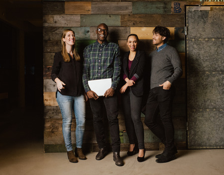 Photo pour Portrait of young professionals laughing while standing together in office. Multi ethnic business team looking happy together. - image libre de droit