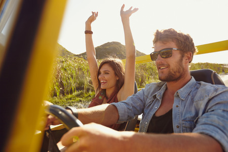 Happy couple enjoying on a long drive in a car. Friends going on road trip on summer day. Caucasian young man driving a car and joyful woman with her arms raised.