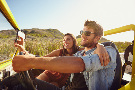 Man driving car with woman taking selfie on her smart phone. Couple having fun on road trip on a summer day.
