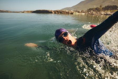 Open water swimming. Male athlete swimming in lake. Triathlon long distance swimming.