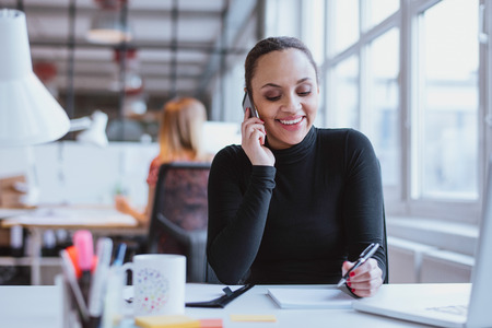Happy young woman sitting at her desk working and answering a phone call.