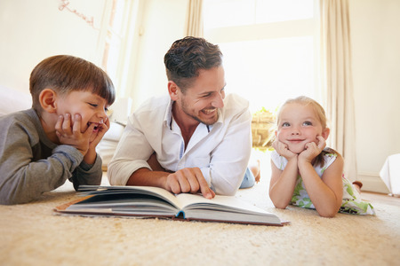 Portrait of happy young family of three lying on floor with a book. Father with two kids reading a story book in living room at home.