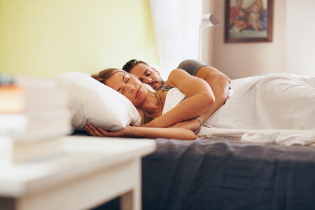 Young adult couple sleeping peacefully on the bed in bedroom. Young man embracing woman while lying asleep in bed.