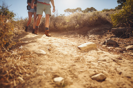Low angle view of two people hiking along a dirt trail in the wilderness.  Couple of hikers walking on country path.