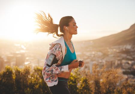 Foto de Portrait of beautiful young woman out for a run on a hot sunny day. Caucasian female model jogging outdoors. - Imagen libre de derechos
