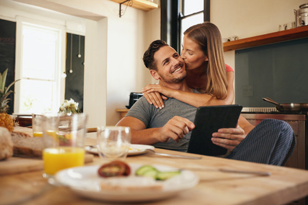 Young man holding a digital tablet while his girlfriend hugs him from behind, giving him a good morning kiss. Young love couple in morning at the kitchen.