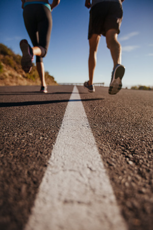 Photo pour Cropped shot of two people running on road. Athletes training on country road. Low angle shot with focus on road. - image libre de droit