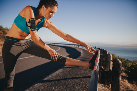 Female runner stretching her legs outdoor before running. Woman doing leg stretch exercises on road guardrail.