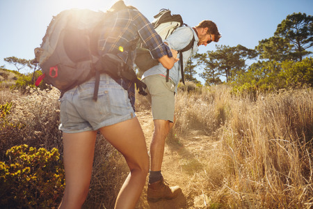 Hiker helping his girlfriend uphill in the countryside. Couple hiking in mountain on a summer day.