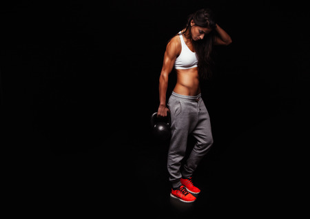 Fitness woman doing crossfit exercising with kettle bell. Fitness instructor on black background. Female model with muscular, fit and slim body.