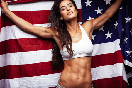 Sporty young woman holding American flag. Fitness female with perfect abs.