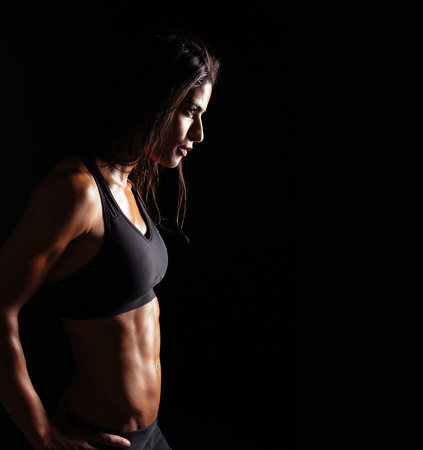 Foto de Image of fitness woman in sports clothing looking away on black background. Young female with perfect muscular body. Determination and confidence. - Imagen libre de derechos