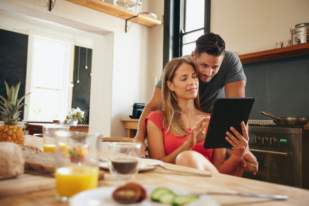 Foto de Young couple in kitchen looking at tablet pc. Man standing by his girlfriend sitting using digital tablet in morning. - Imagen libre de derechos