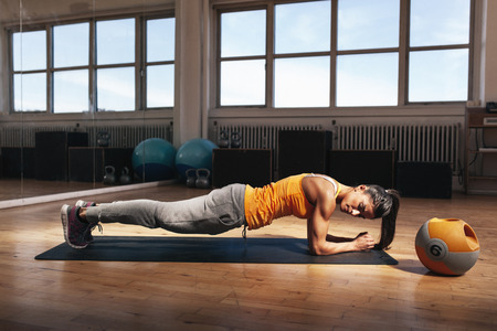 Foto de Young muscular woman doing core exercise on fitness mat in the gym. Fit female doing press-ups during the training in the health club. - Imagen libre de derechos