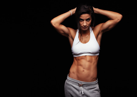 Foto de Muscular woman wearing fitness clothing posing against black background. Caucasian female model with perfect abs. - Imagen libre de derechos