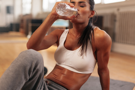 Fitness woman drinking water from bottle. Muscular young female at gym taking a break from workout.
