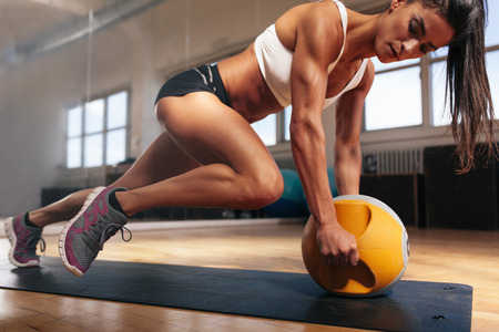 Muscular woman doing intense core workout in gym. Strong female doing core exercise on fitness mat with kettlebell in health club.