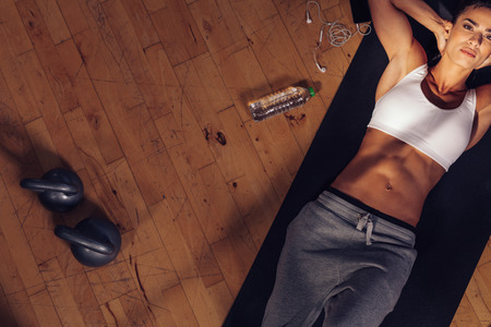 Photo for Top view of fitness model lying on exercise mat. Overhead shot of fitness instructor tired resting on mat with water bottle, mobile phone and kettle bell on floor. - Royalty Free Image