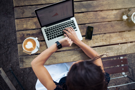 Photo for Overhead view of young woman checking time on her smartwatch while working on her laptop at a cafe. Top view shot of female sitting at a table with a cup of coffee, laptop and mobile phone. - Royalty Free Image