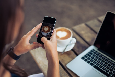 Foto de Woman taking a picture of a coffee cup with her smart phone while sitting at a coffee shop. - Imagen libre de derechos
