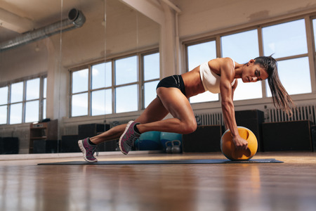 Foto de Portrait of a fit and muscular woman doing intense core workout with kettlebell in gym. Female exercising at crossfit gym. - Imagen libre de derechos