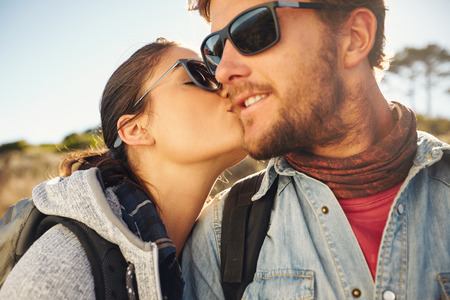 Loving young tourist couple hiking. Young woman kissing cheek of her boyfriend, outdoors on a hike.