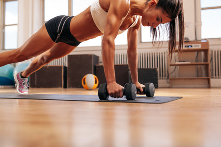 Foto de Strong young woman doing push ups exercise with dumbbells on yoga mat. Fitness model doing intense training in the gym. - Imagen libre de derechos